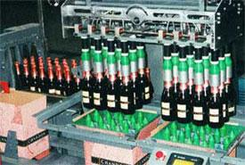 Pick-and-place case packer loads two cases simultaneously. Pneumatic inflating bladders handle wine bottles gently, without damaging corks, wire hoods or foil, and essentially eliminate label scuffing during the packing process.