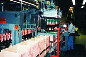 Reciprocating robotic pick-and-place unit transfers bottles from infeed conveyor to cases, which enter machine on parallel conveyor. Grids on top of cases aid packing.