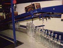 Electronics synchronize decaser bottle feed with filler speed, for optimum line efficiency
